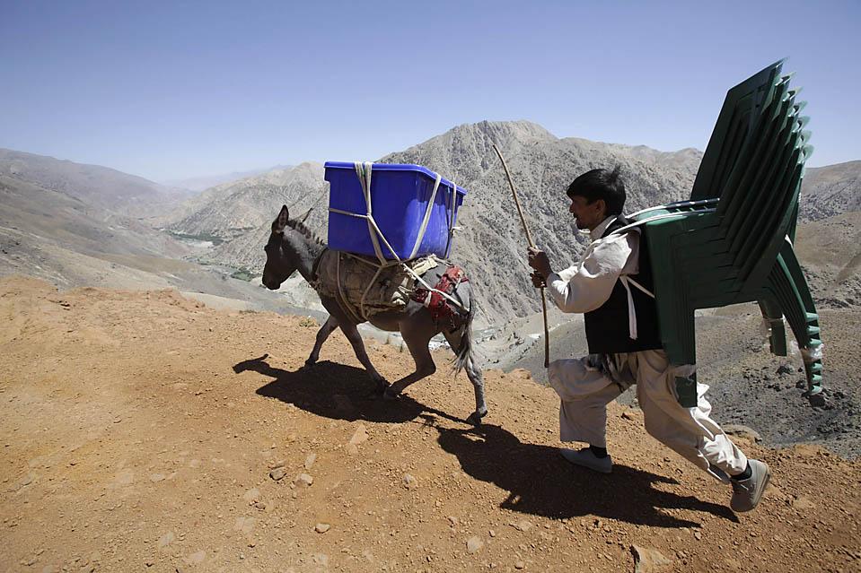 """2) Мужчина ведет осла, перевозящего грузы, необходимые для проведения выборов на сельских избирательных участках в Sighawar, в Афганистане, в среду. По стране прокатилась волна нападений, в которой погибли, по меньшей мере, шесть работников избирательных участков. Вчера нынешний президент Хамид Карзай сказал: """"Я надеюсь, что завтра наши соотечественники - миллионы наших соотечественников - придут и проголосуют за ... стабильности в стране, за мир и развитие"""". (Lucy Nicholson/Reuters)"""
