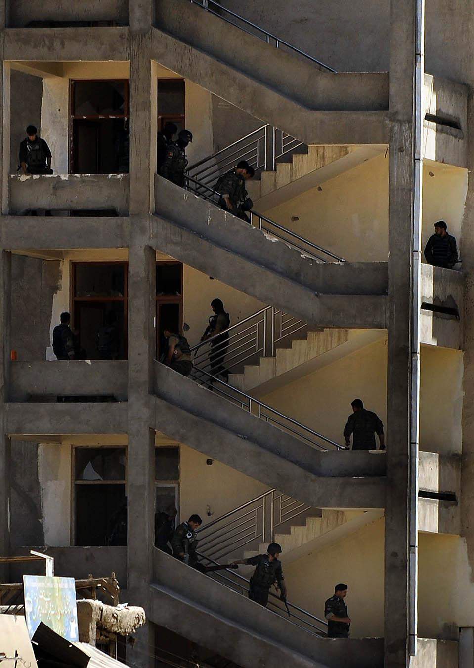 """3) Афганские силы безопасности несут труп стрелка, после штурма здания банка в Кабуле. Во время штурма были убиты трое боевиков, которые захватили банк. Движение """"Талибан"""" взяло на себя ответственность за это нападение. Тем временем, американские военные заявили, что трое американских солдат были убиты в результате двух инцидентов, в южной части Афганистана. (Massoud Hossaini/Agence France-Presse/Getty Images)"""