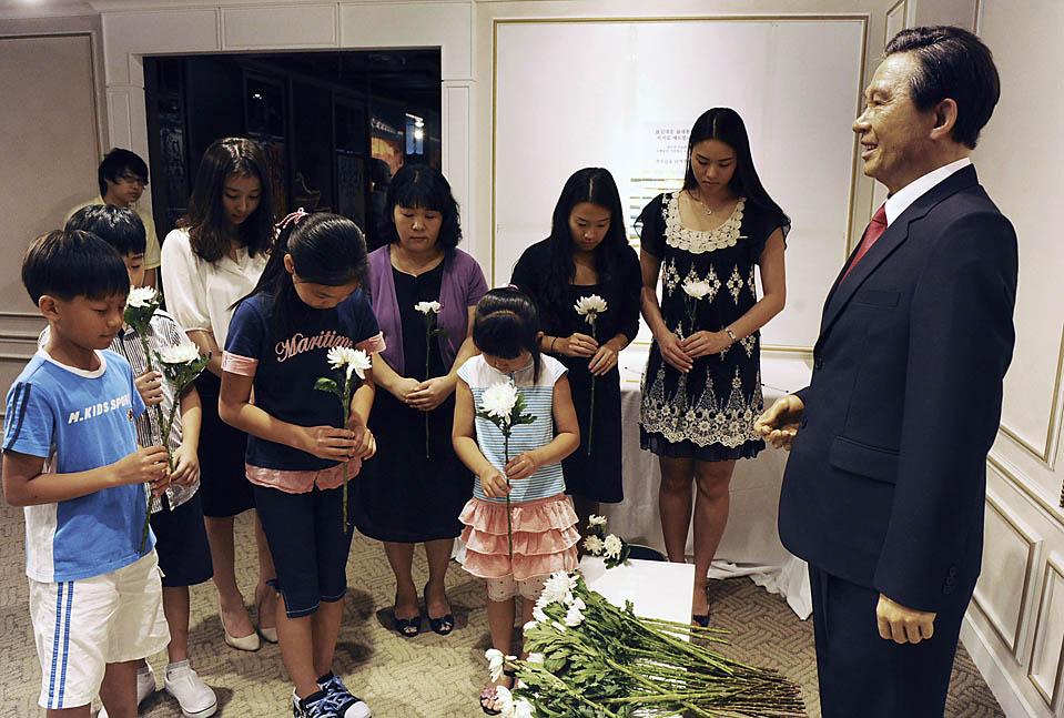 6) Люди стоят у восковой статуи бывшего южнокорейского президента Ким Дэ Чжуна в сеульском музее. Г-н Ким скончался во вторник в возрасте 85. (Huh Kyung/Newsis via Reuters)
