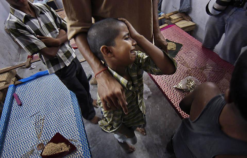 7) Малолетний рабочий одной из фабрик плачет после того, как был спасен в ходе совместной операции полиции и неправительственных организаций в Нью-Дели среду. По данным НПО, 94 детей-работников, в возрасте от 9 до 14 лет, были спасены из цехов, в которых изготовляется украшения бинди (украшения на лоб) и вышивка. (Adnan Abidi/Reuters)