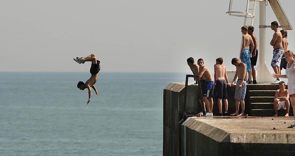 12) Мальчик прыгает с волнореза в английском городе Гастингс. (Peter Macdiarmid/Getty Images)