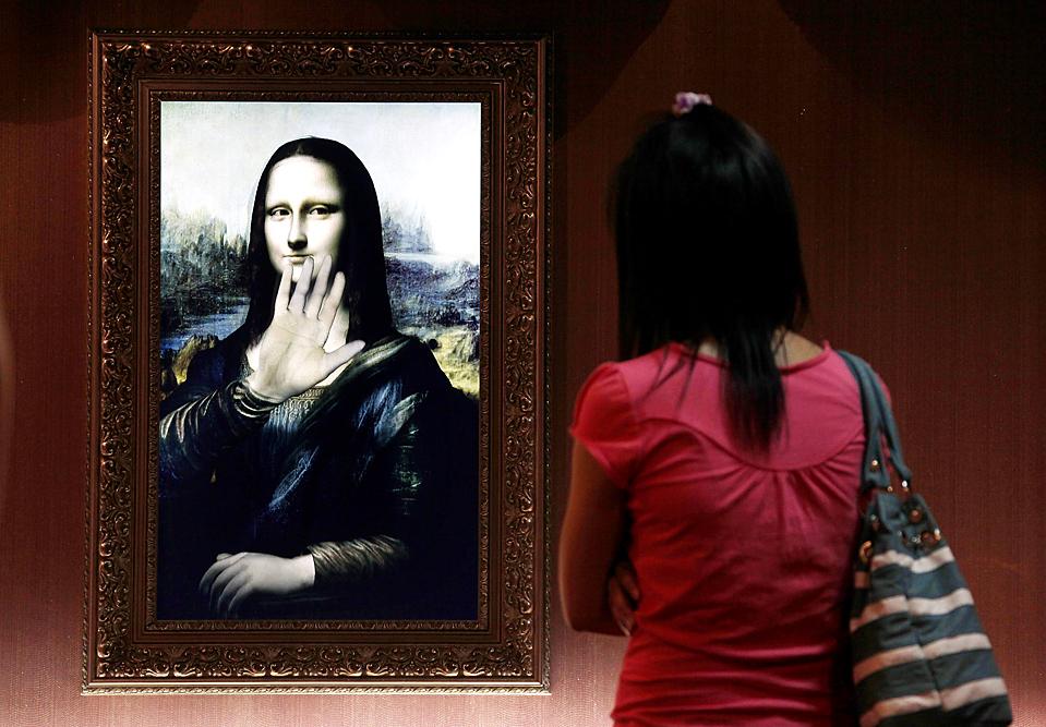 """4) Посетительница Пекинской Живой галереи смотрит на трехмерную, голографическую версию картины 16-го века """"Мона Лиза"""", которая машет ей рукой. Голографическая версия всемирно известной картины движется, и отвечает на вопросы. Это – одна из нескольких классических картин на выставке. (David Gray/Reuters)"""