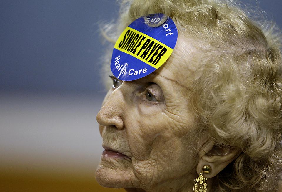 5) 89-летняя Роберта Кроуфорд с наклейкой в поддержку системы единой медицинской страховки  во «Флоридском альянсе пенсионеров-американцев» на пятом ежегодном совещании муниципалитета по вопросам реформы здравоохранения в Делрей Бич, штат Флорида. (Lynne Sladky/Associated Press)