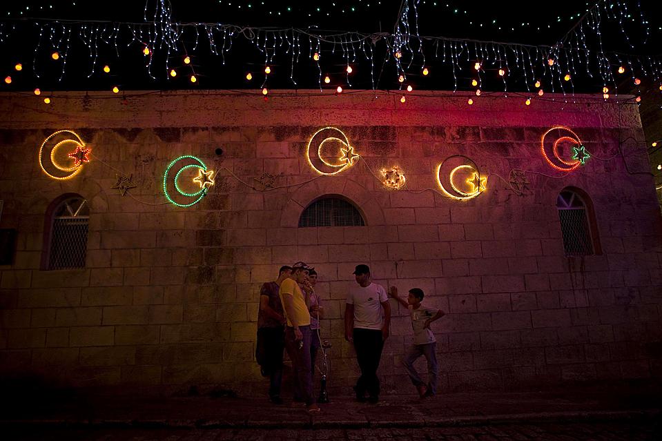 6) Палестинцы курят кальян, а на фоне горят праздничные огни в честь Рамадана. Снимок сделан в Старом городе Иерусалима. В субботу мусульмане во всем мире отмечают начало священного месяца Рамадан. (Bernat Armangue/Associated Press)