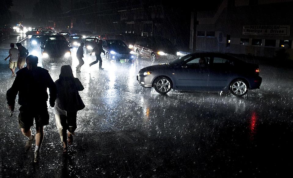 89) Пешеходы и автомобилисты на перекрестке в городе Питерборо, провинция Онтарио, Канада, во время отключения электроэнергии. Примерно 5500 человек остались без власти, после сильных гроз в этом районе. (Clifford Skarstedt Jr./Associated Press)