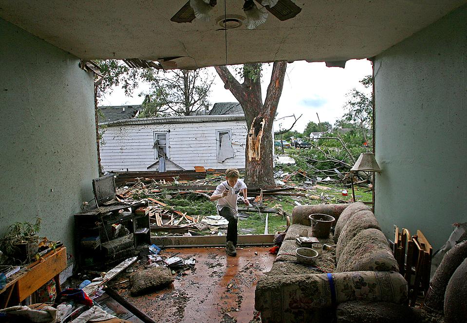 9) 13-летний Алек Такер заходит в свой дом через одну из стен гостиной, которая была разрушена, после того, как торнадо прошел по городу Вильямсвиль, штат Иллинойс. Торнадо повредил в Вильямсвиле 25 домов, включая церковь. (Ted Schurter/Associated Press)