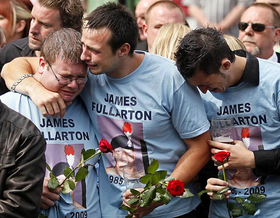 13) Семья и друзья младшего капрала британца Джеймса Фуллартона скорбят у его гроба, в то время, как похоронная процессия проходит по улицам Вуттон Бассетт, в Уилтшире, на юге Англии. Тела четырех британских военнослужащих, погибших в Афганистане, были доставлены в Великобританию в пятницу. (Shaun Curry/AFP/Getty Images)