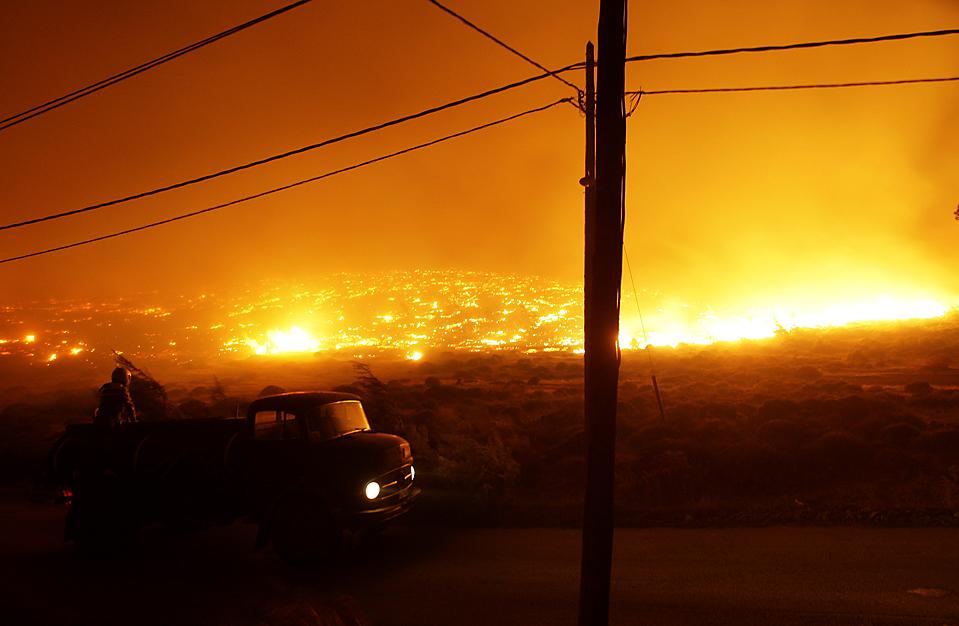 13) Местный житель наблюдает за пожаром на горе Пентели в Греции. Сильные пожары несколько дней подряд бушевали под Афинами, разрушая дома и вынуждая людей к бегству. (Petros Giannakouris/Associated Press)