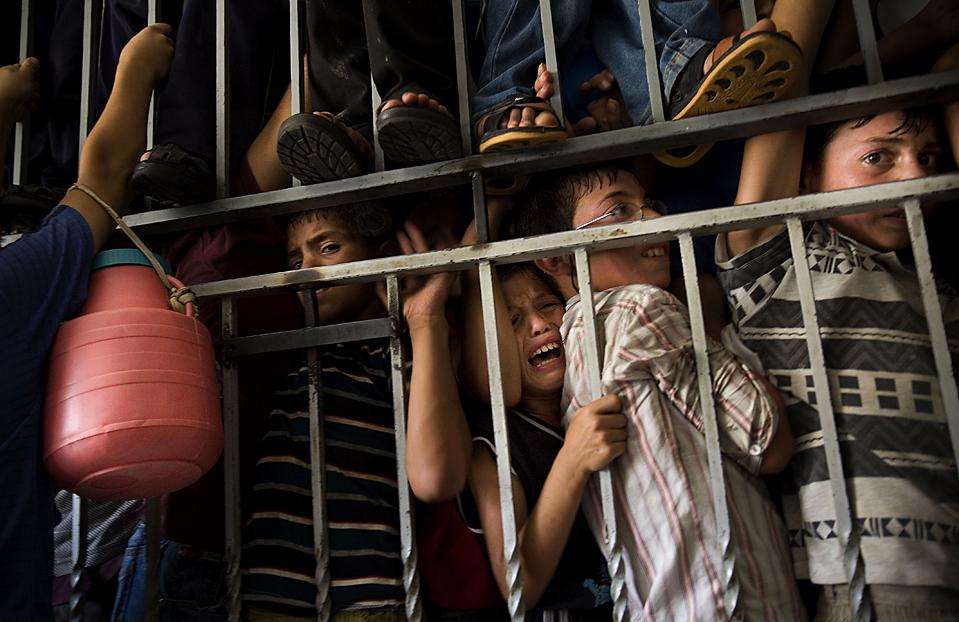 10) Палестинские дети пытаются получить продовольственные пайки в Хевроне, на Западном берегу. (Bernat Armangue/Associated Press)