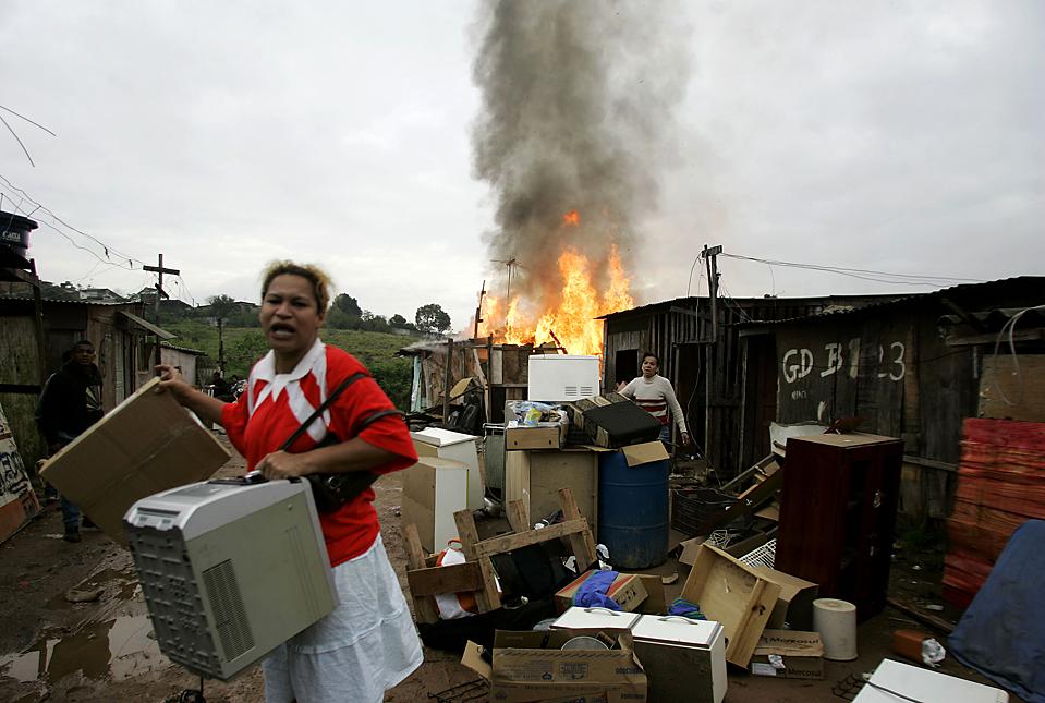 8) Люди собирают свои вещи в трущобах Capao Редондо в Сан-Паулу, Бразилия. Местные жители подожгли машины и дома, после того, как полиция выселила сотни семей из незаконно занятых строений. (Nelson Antoine/Associated Press)
