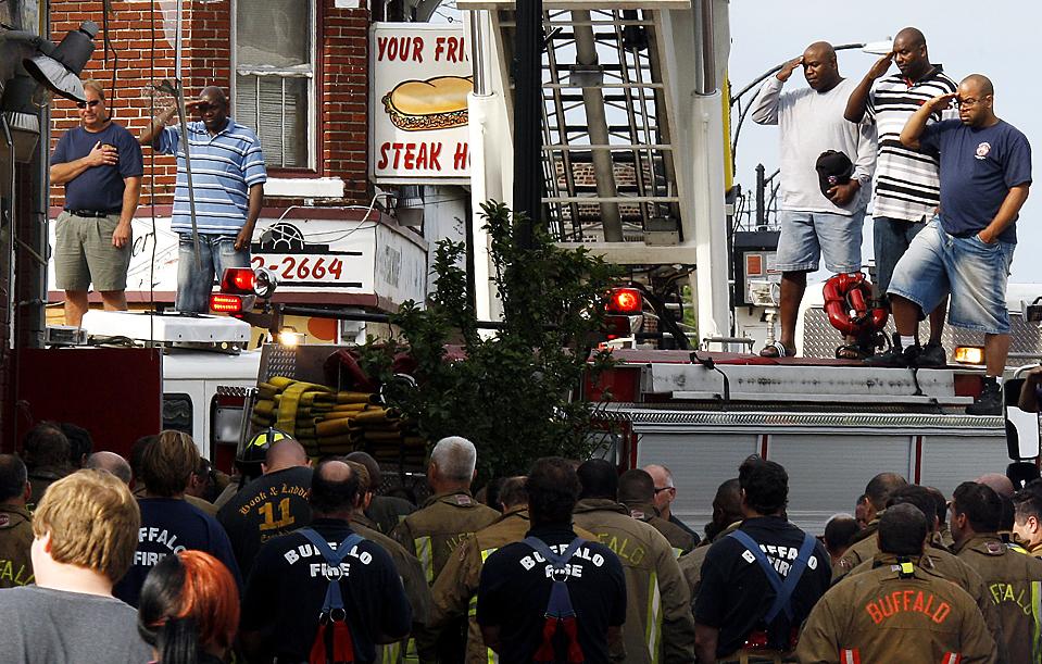 5) Пожарные салютуют во время того, как устланные флагом каталки с телами их товарищей вывозят из здания в Буффало, штат Нью-Йорк. Второй этаж горящего магазина рухнул в подвал, в результате чего погибли двое пожарных. (David Duprey/Associated Press)