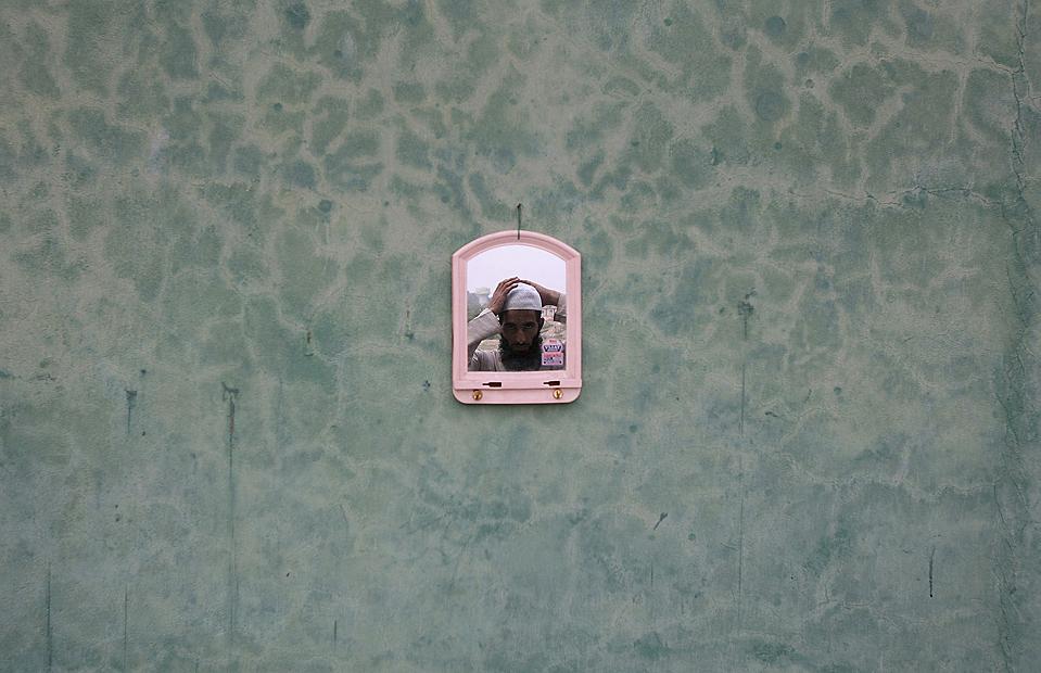 1) Мужчина-мусульманин смотрит на себя в зеркало. Снимок сделан во время священного месяца Рамадан в индийском городе Джамму, Индия. В соответствии с одним из пяти столпов ислама в течение месяца Рамадан правоверные мусульмане должны поститься от наступления утреннего намаза до наступления вечернего намаза, т.е. от рассвета до заката. (Mukesh Gupta/Reuters)