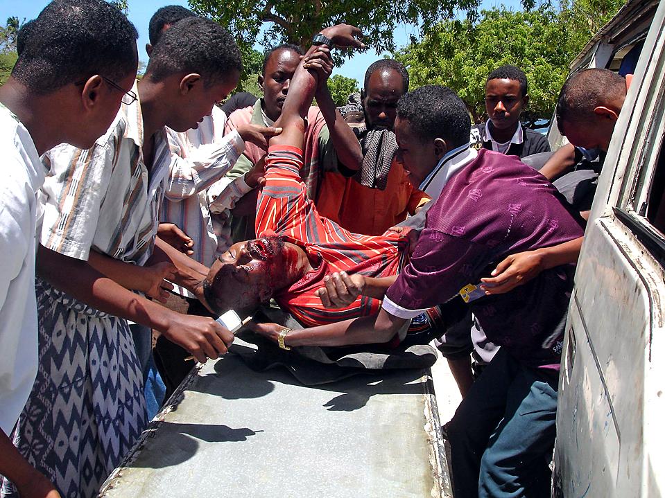 5) Люди кладут на тележку раненного в перестрелке  между исламистскими повстанцами и правительственными силами в Могадишо, столице Сомали. Повстанцы угрожают увеличить число нападений во время Рамадана, но посланник ООН в Сомали призвал сомалийцев объединиться во время священного месяца. (Farah Abdi Warsameh/Associated Press)