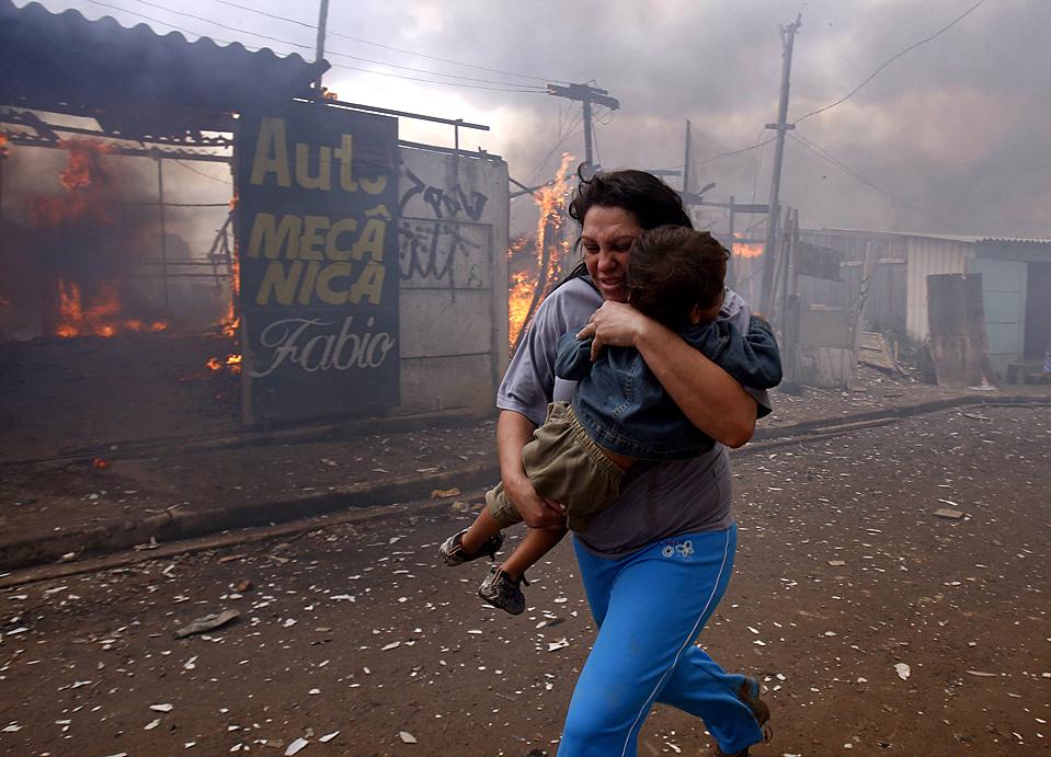 7) Женщина несет ребенка мимо горящего дома в трущобах Capao Редондо на окраине Сан-Паулу, Бразилия. Жители подожгли дома в знак протеста после того как полиция и чиновники выселили 800 семей из трущоб, которые были незаконно заняты с 2007 года. (Paulo Whitaker/Reuters)