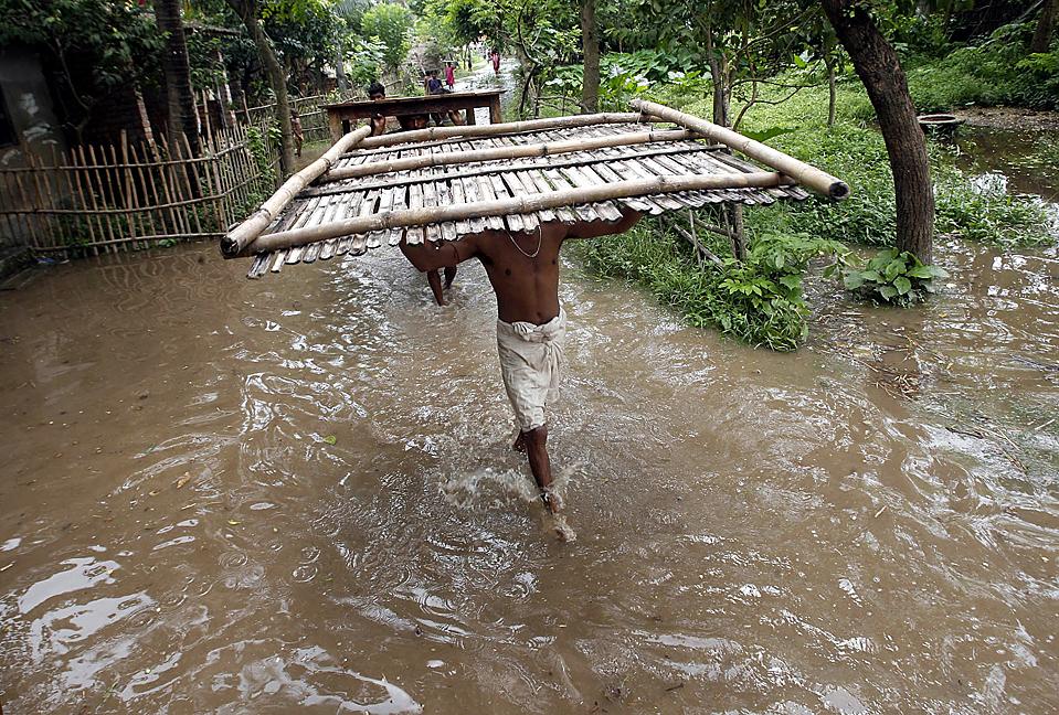 15) Люди несут свои вещи через бульвар в затопленной деревне Баниканто Толи в восточном индийском штате Западная Бенгалия. В этом году в сезон летних муссонов с первой половине июня по сентябрь в Индии прошли необычно скудные дожди. (Rupak De Chowdhuri/Reuters)