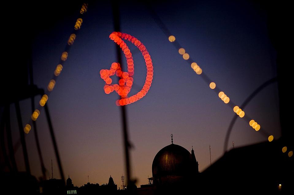 7) Праздничные фонари горят рядом с мечетью Аль-Акса, на фоне святынь Иерусалима, во время Рамадана во вторник. (Bernat Armangue/Associated Press)