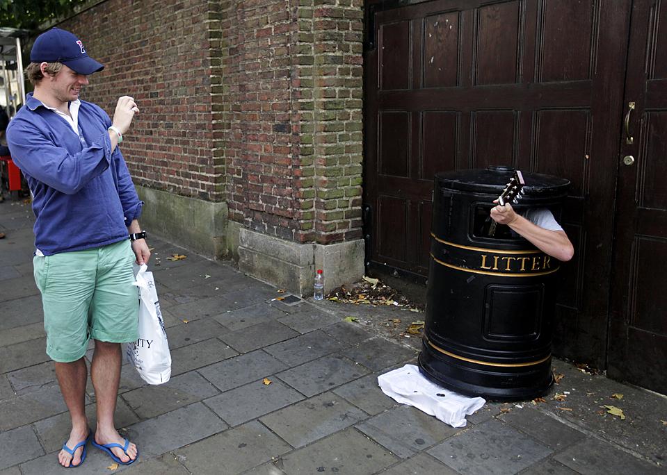 11) Турист фотографирует уличного музыканта, который сидит внутри мусорного бака в Кембридже, Англия. (Lefteris Pitarakis/Associated Press)