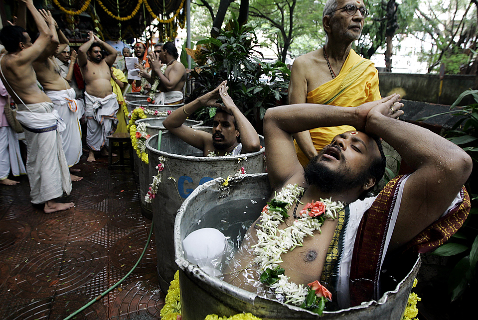 12) Индусы совершают ритуал Варуна яджна, чтобы умиротворить бога дождя в Мумбаи. Священники стояли в воде более четырех часов и молились о дожде. Сезон муссонов в этом году в Индии начался поздно, а количество осадков было ниже нормального уровня. (Rajanish Kakade/Associated Press)