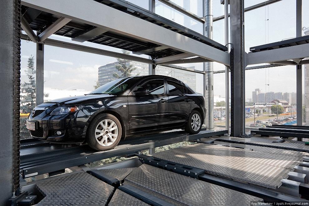10) Сначала система забирает пустую палету, затем платформа опускает вниз, где на на нее заезжает автомобиль.