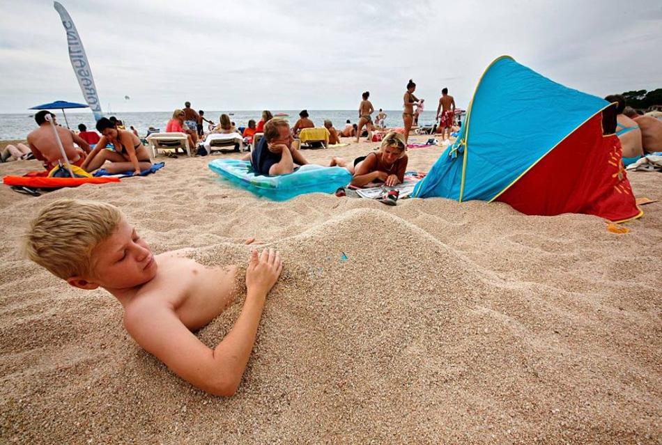 10. 12-летний Алекс закопал себя в песок, в то время как другие члены семьи Таяс из Южного Йоркшира отдыхают на пляже на каникулах в Льорет-де-Мар, Испания. (Cate Gillon, Getty Images)