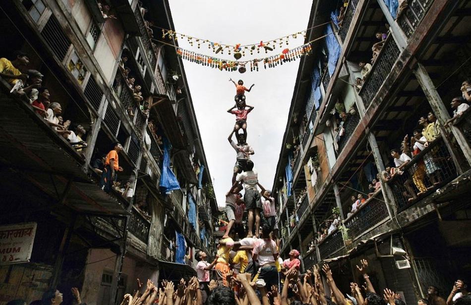 10. Религиозные фанаты образуют живую пирамиду, чтобы добраться до сосуда с маслом во время празднования «Джанмаштами» - годовщины рождения Господа Кришны в Мумбаи, 14 августа. (Rajanish Kakade, AP)
