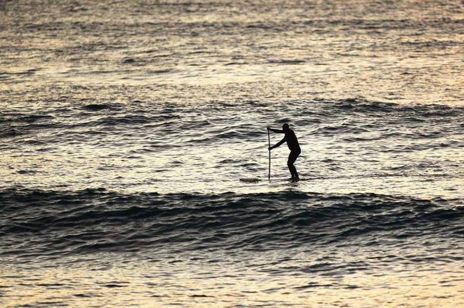 8) Пол Хоукинс плывет по волнам на своей доске на пляже Куинсдиф 1 мая 2009 года в Сиднее, Австралия. Современный стоячий серфинг с веслом произошел на Гавайях в 1960 году, когда инструкторы по серфингу следили за своими учениками  в воде. Сейчас этот вид спорта быстро набирает популярность благодаря своей пользе, которую он приносит сердечно-сосудистым органам. (Cameron Spencer, Getty Images)