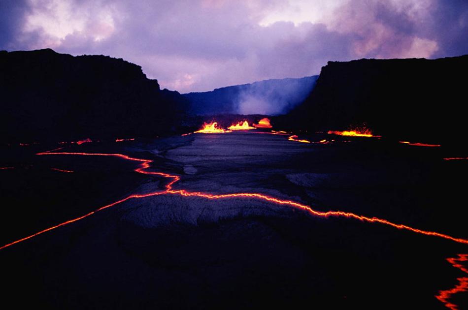 11. Национальный парк «Вулканы Гавайев» расположен в юго-восточном регионе Большого Острова и известен своим действующим вулканом Килауэа. На этом снимке лава течет по трещинам в сумерках.