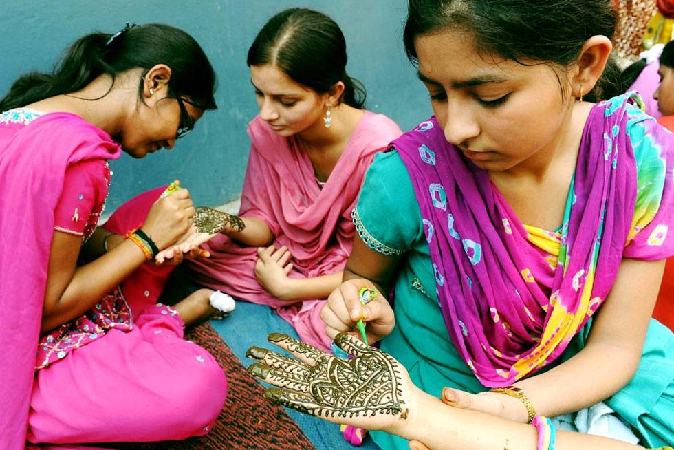12. Школьницы украшают друг другу руки хной во время фестиваля Тидж в Амритсаре, Индия, 25 июля. (Narinder Nanu/AFP /Getty Images)