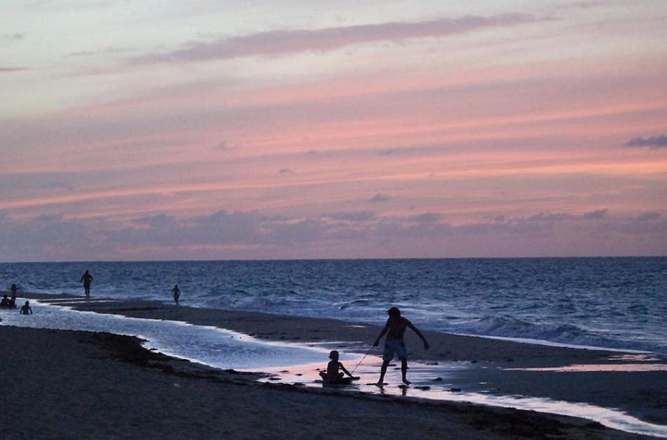 12. Дети играют на побережье в Сан Хуане, Пуэрто-Рико, выжимая из этого дня, проведенного на пляже, все, что можно. (Brennan Linsley, AP)