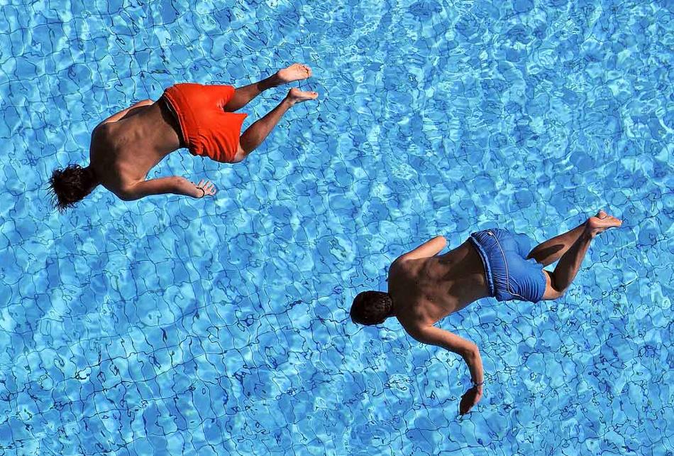 12. Молодые люди прыгают с вышки в бассейн в Штутгарте, Германия, 7 августа. (Daniel Maurer, AP)