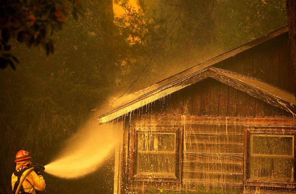 12. Пожарный окатывает водой строение в округе Санта Круз, Калифорния, 13 августа, чтобы спасти его от приближающихся пожаров. (Noah Berger, AP)