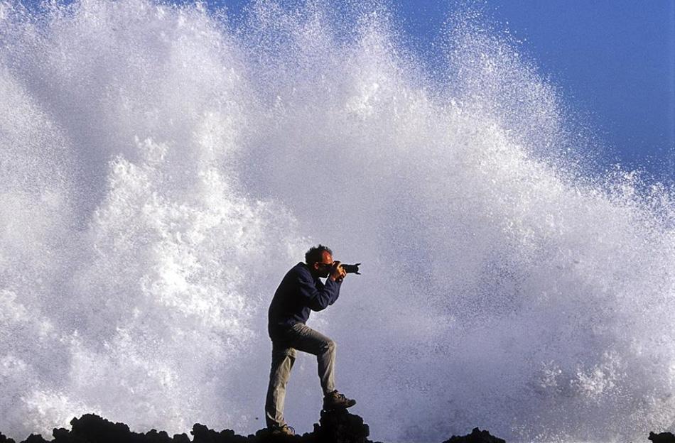 12) Фотограф у Атлантического океана на Ла Пальма, Канарские острова, Испания. Рассказывает фотограф Карлос Виргили Райб: «Мы фотографировали на следующий день после крупного шторма. Я увидел этот утес, о который каждые 30 секунд разбивались волны. Я попросил друга попозировать для «мокрой фотографии». Спустя несколько снимков нам все же удалось «зацепить» большую волну». (Carlos Virgili Ribe, Nature's Best Photography)
