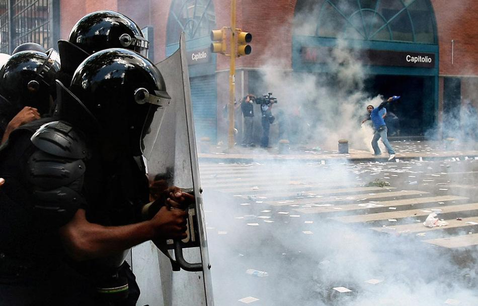14. Штурмовой отряд полиции столкнулся с демонстрантами перед зданием Парламента в деловом центре Каракаса, Венесуэла, 13 августа. Беспорядки начались из-за принятия нового закона об образовании. (Thomas Coex, AFP/Getty Images)
