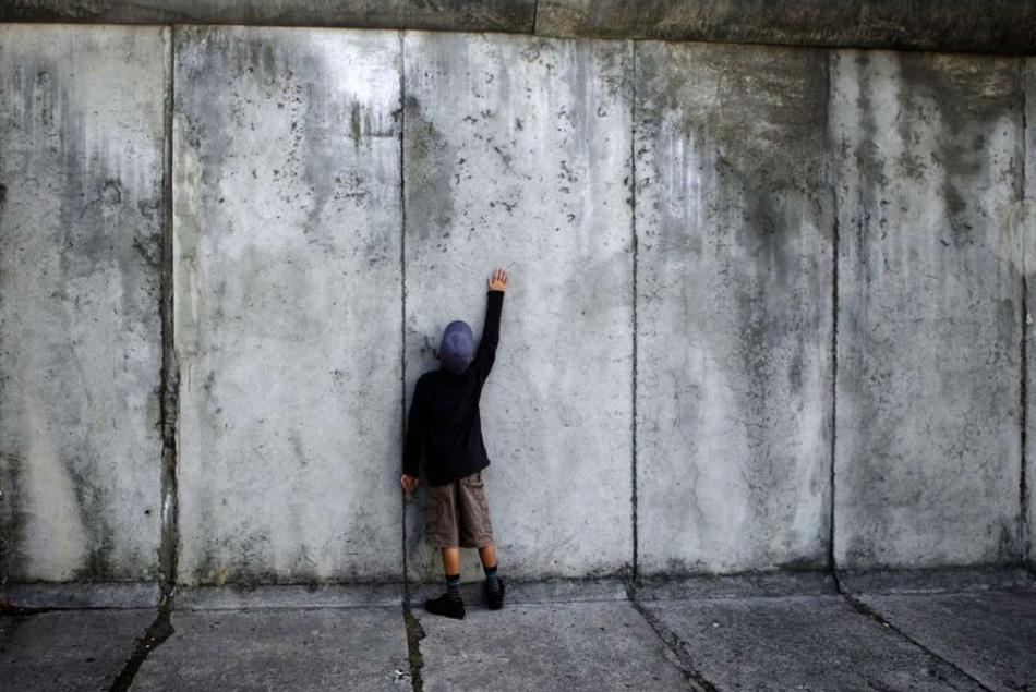 15. Мальчик дотрагивается до бывшей Берлинской стены в день 48-ой годовщины ее создания в Берлине 13 августа. (Markus Schreiber, AP)