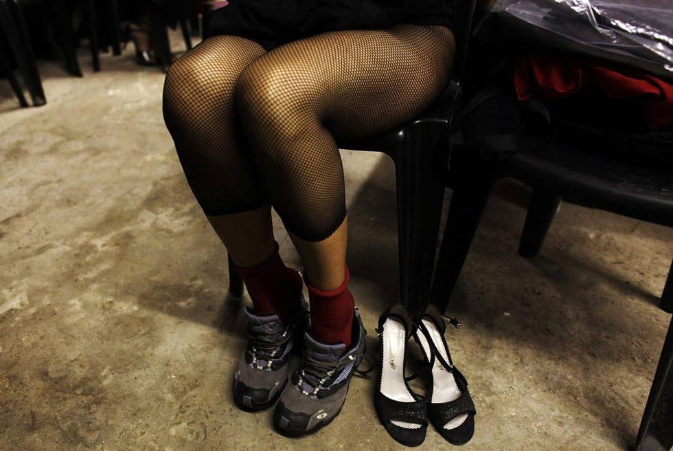 15. Танцовщица переобувается в кроссовки после участия в отборочном соревновании седьмого Чемпионата Мира по танго 25 августа. (Natacha Pisarenko, AP)