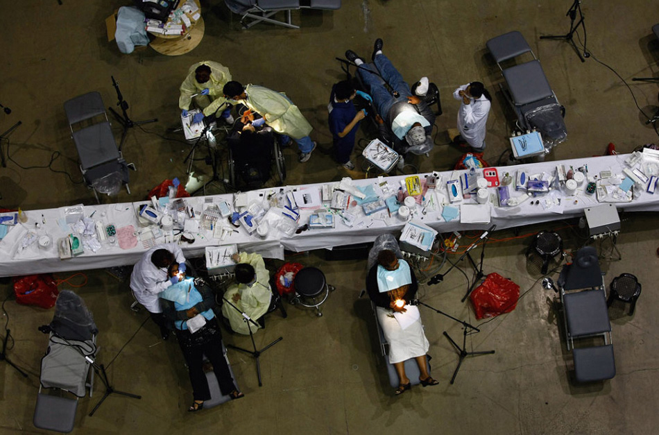 16. Пациентам лечат зубы в бесплатной клинике на специальной площадке в Инглвуде, Калифорния, 12 августа. С 11 по 18 августа некоммерческая организация «Remote Area Medical» (RAM) проводит самую крупную в стране бесплатную консультацию. Сотни докторов, дантистов, оптиков, медсестер и других медицинских сотрудников добровольно проводят лечение людей, не имеющих страховки. (John Moore, Getty Images)