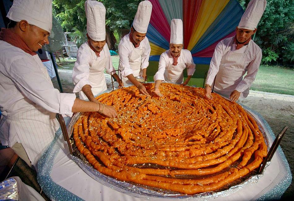 17. Индийские повара придают последние штрихи огромному джалеби – индийской сладости диаметром 1,65 м  и весом 26,99 кг – перед фестивалем «Ракша Бандхан» в Ахмадабаде, Индия, 3 августа. (Ajit Solanki, AP)