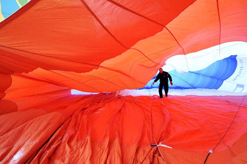 19. Воздухоплаватель осматривает внутреннюю часть воздушного шара во время 31-й Международной недели воздушных шаров на горнолыжном курорте в Шато д'О в Швейцарских Альпах 25 января. (Dominic Favre, Keystone /AP)