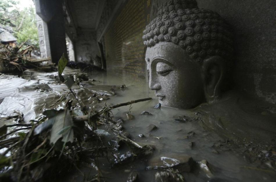 19. Обломки и сточные воды от наводнения после тайфуна Моракот окружают голову статуи Будды в храме округа Гаосюн, южный Тайвань, 11 августа. (AP)