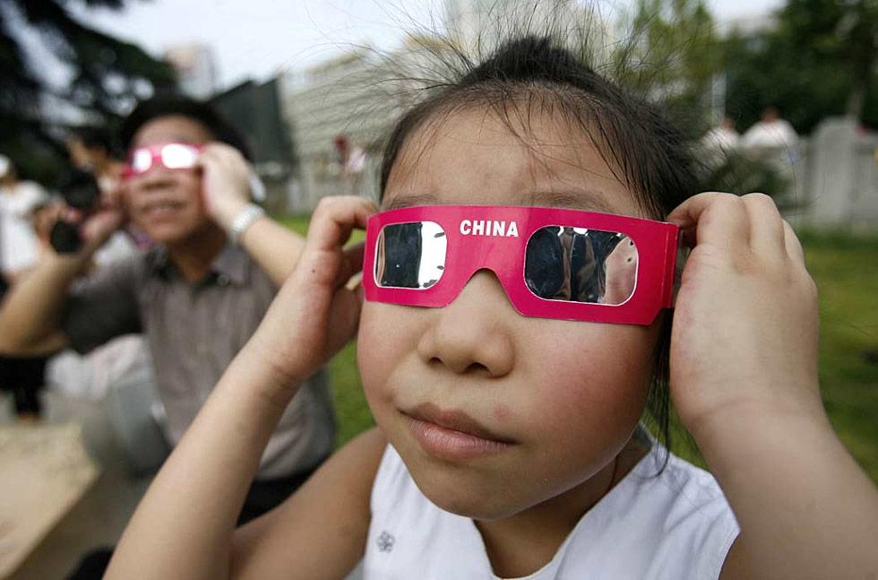 20. Китайские дети наблюдают за солнечным затмением в провинции центрального Китая Хубэй 22 июля. Самое длительное солнечное затмение 21 века погрузило миллионы людей во временную темноту. (AFP /Getty Images)