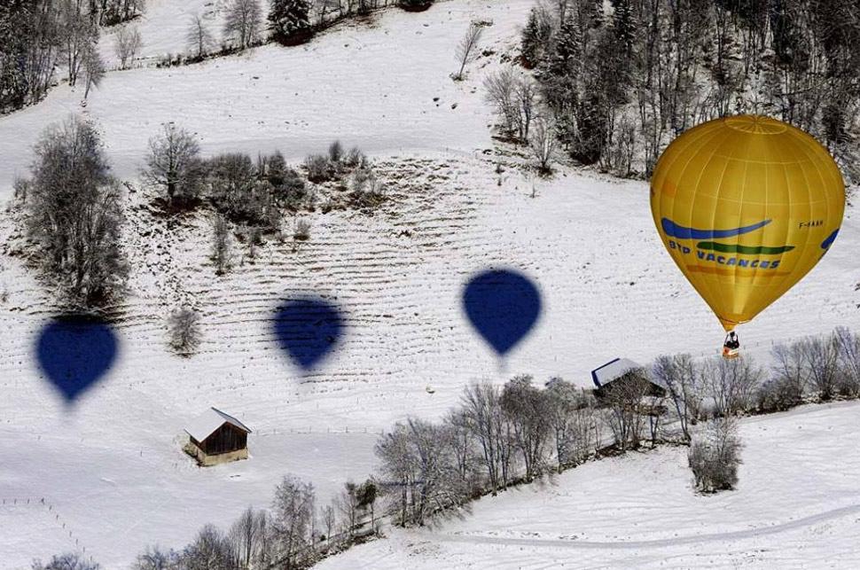 21. Тени, отбрасываемые воздушными шарами, падают на заснеженный пейзаж во время 31-й Международной недели воздушных шаров в Шато д'О, Швейцария, 25 января. (Simone Zimmerli, Keystone /AP)