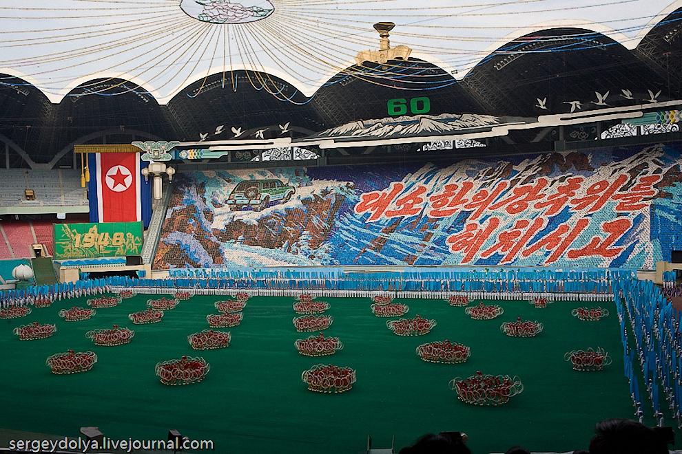 """20) Текст на панно справа от внедорожника: """"Даже в холодную погоду наш Великий Руководитель, товарищ Ким Чен Ир ездит на машине""""."""