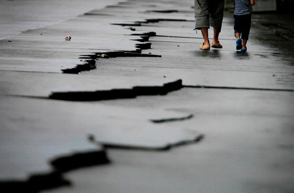21. Отец и сын гуляют по трещинам после землетрясения в 6,5 баллов в порту Яцу в Японии во вторник 11 августа. Землетрясение произошло в Токио и соседних районах во вторник ночью, став причиной задержки поездов и закрытия двух ядерных реакторов во избежание риска. (Itsuo Inouye, AP)
