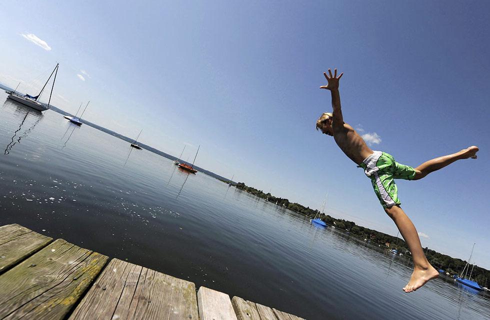 22. Деннис прыгает в озеро в южной Германии теплым летним деньком при температуре где-то 27 градусов по Цельсию 21 июля. (Christof Stache/AP)
