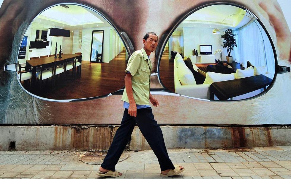 23. Человек проходит мимо рекламного щита нового строительного комплекса в Пекине 21 июля. Экономика Китая выросла на 7,9% во втором квартале 2009 года, об этом объявило правительство страны на прошлой неделе.(Frederic J. Brown/AFP /Getty Images)