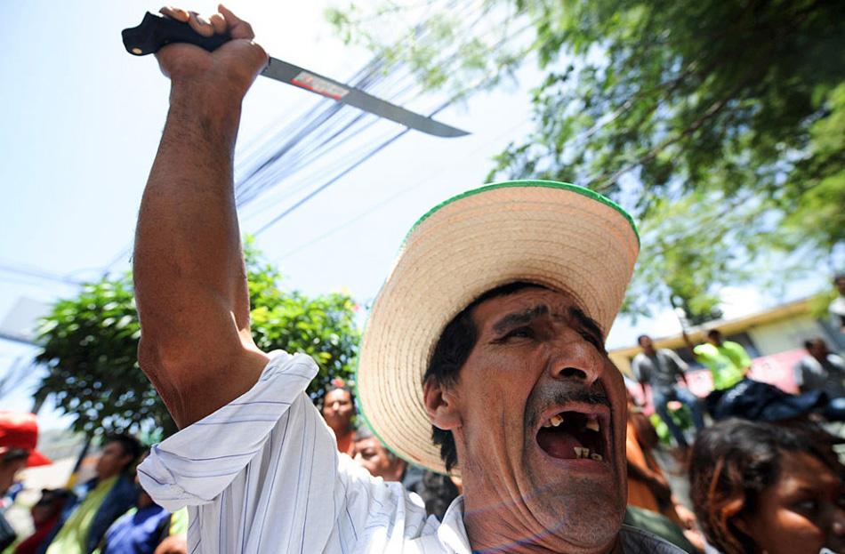 23. Гондурасский сельский житель размахивает мачете и кричит во время демонстрации за возвращение свергнутого с поста президента Мануэля Селайи 10 августа в Тегусигальпе. (Orlando Sierra, AFP/Getty Images)