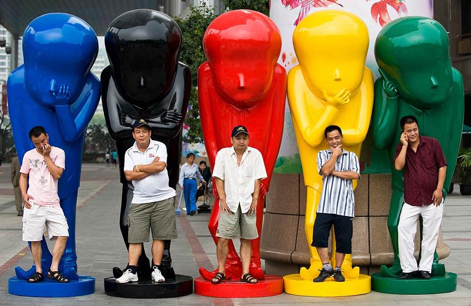 24. Китайцы позируют фотографу на статуях возле торгового центра в Пекине, Китай, 30 июля. (Andy Wong, AP)