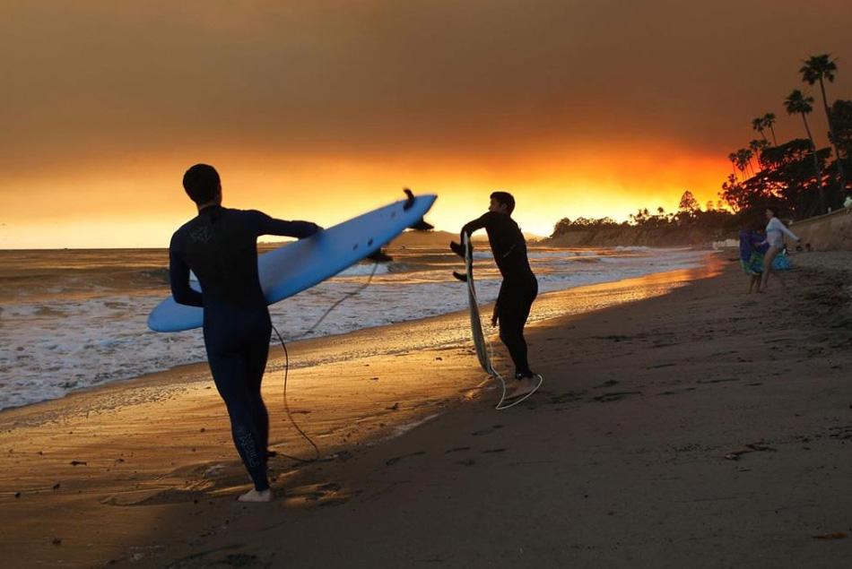 17) Серферы входят  в воду в густом дыме от пожара Иесусита на пляже Баттерфляй 7 мая 2009 года в Монтесито, к югу от Санта- Барбары, штат Калифорния. (David McNew, Getty Images)