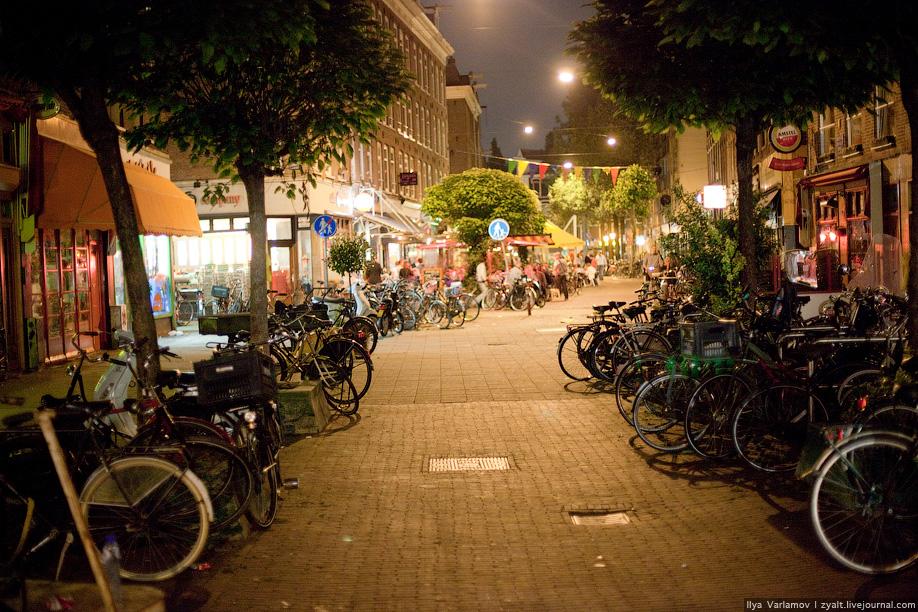 25) Типичная улица, все обочины заставлены велосипедами.