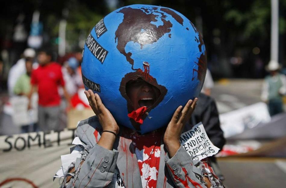 27. Антиглобалист выкрикивает лозунги во время марша против саммита Северной Америке в Гвадалахаре, Мексика, 9 августа. (Eduardo Verdugo, AP)